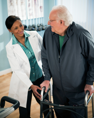 Active senior male walking with walker with physical therapist.
